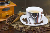 Fotografie cup of coffee, coffee beans and old coffee grinder