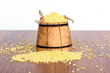Wooden bucket with millet on a wooden table. The most useful and tasty cereal porridge out of it.