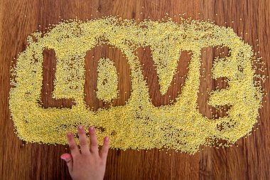 Declaration of love painted millet. Child draws on a table with crumbles millet.