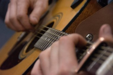 Guitar deck and guitarist hands closeup. Capo on the fretboard of a guitar. Blurred guitar background
