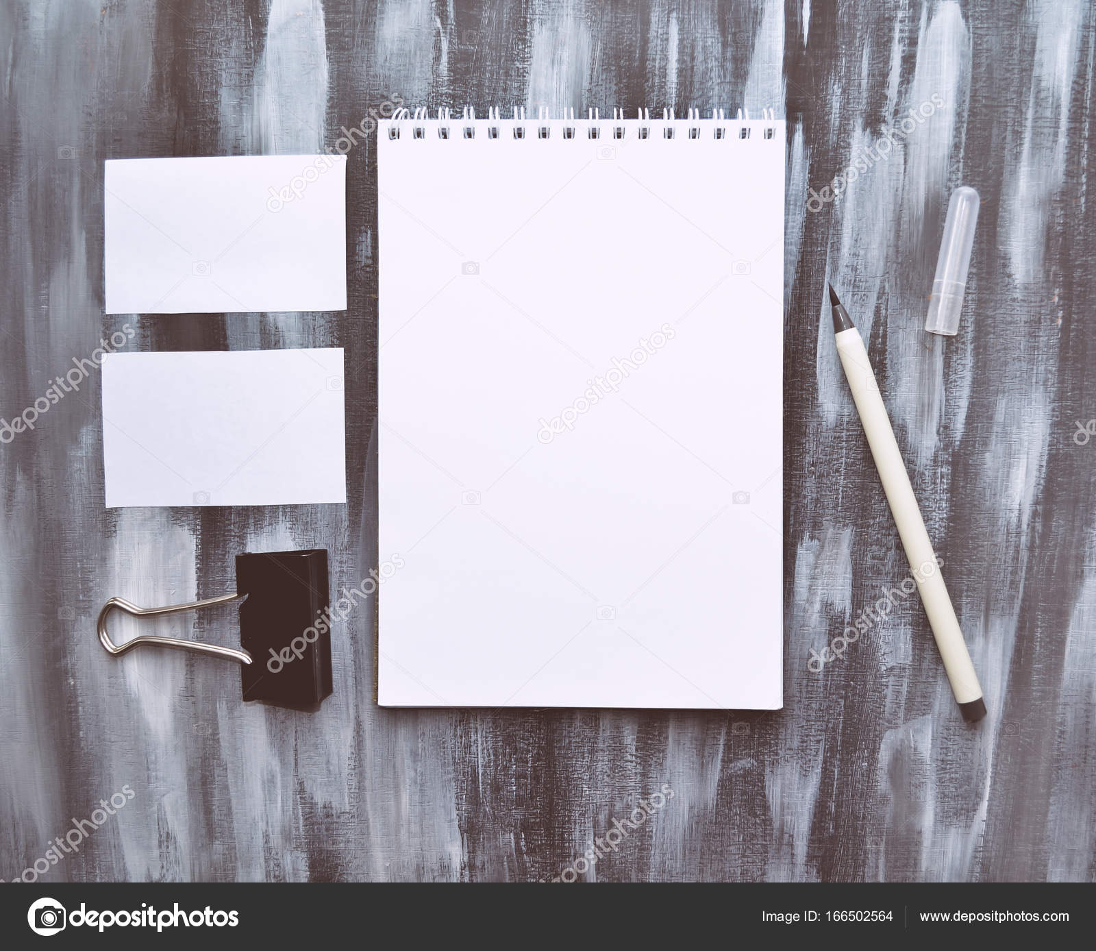 White opened notepad, business cards, pen and paper holder on a ...