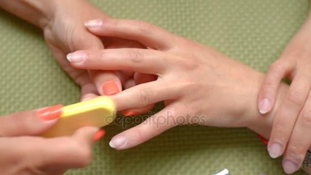 Kosmetička čistí nehty, pilník.
