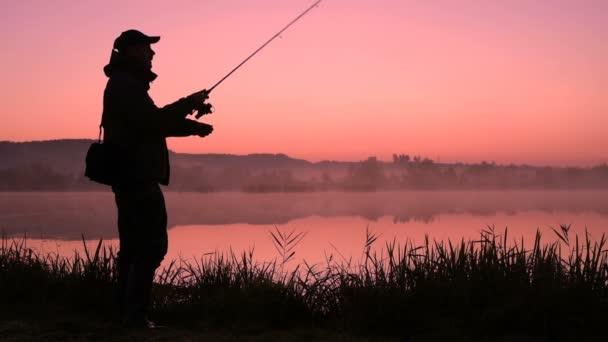Silueta rybáře při východu slunce. Rybář na ranní rybaření. Silueta rybáře při západu slunce. sportovní rybolov koníček. Ranní rybaření na úsvitu
