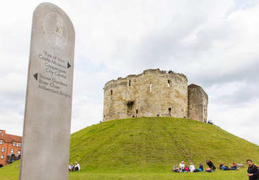 Clifford's Tower in York on green grass and road sign