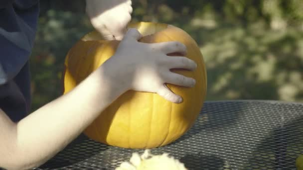 Malý chlapec tahy lžíci Halloween strašidelné hlavy. Dětské ruce vyřezat halloween dýňový strašák