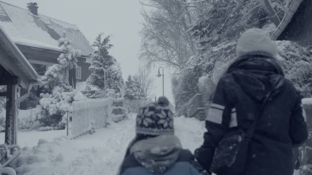 Zasněžené ulice horská města s pěší žena a chlapec, vesnice sněhová kalamita. Zimní krajina, padající sníh. Vše je kryté, čerstvé prášek. Zimní atmosféru, Vánoční pozadí