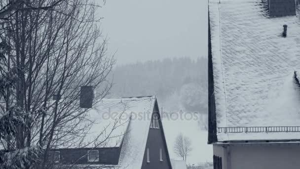 Zasněžené střechy rodinných domů. Ulice města v horské vesnici sněhová kalamita. Zimní krajina s padajícím sněhem. Vše je kryté, čerstvé prášek. Zimní Vánoční pozadí