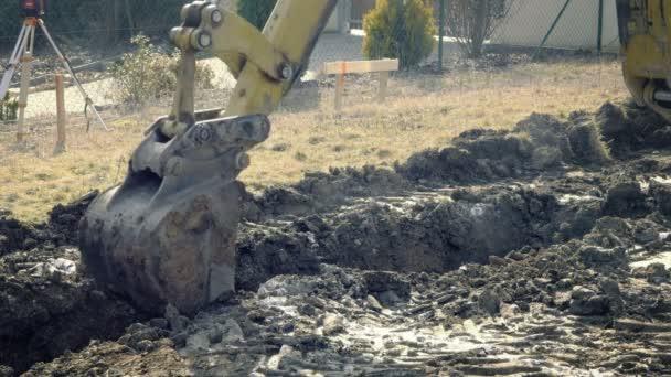 Velký bagr je kopání základů domu. Hloubení díry. Stavební stroje, zemní práce. Žlutý bagr pracuje na budování. Statické den stabilizován v-log výstřel. Plechovka kope v jílu.