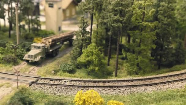 Model railroad track  Miniature train runs through the curve  Trees and  truck with wooden trunks on the body in background  Rail transportation,  entertainment toy industry