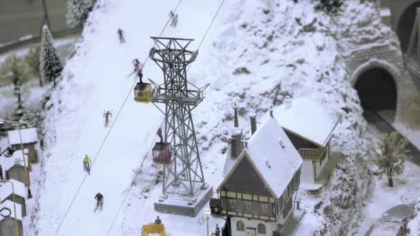 Mountain lift on ski slope with skiers  Miniature model railroad track   Transportation entertainment toy industry