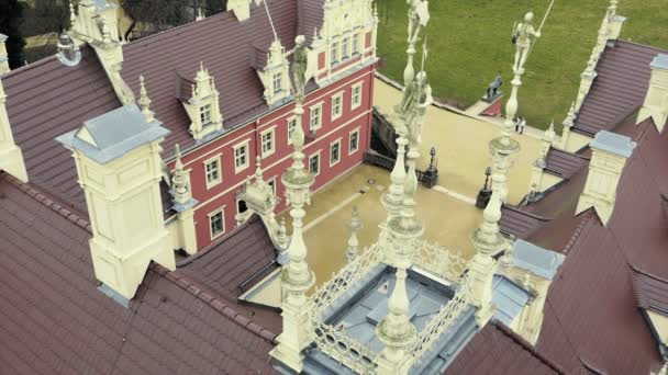 View from tower on roof of classicist castle with red facade. Monumental palace with moat, sculptural decoration