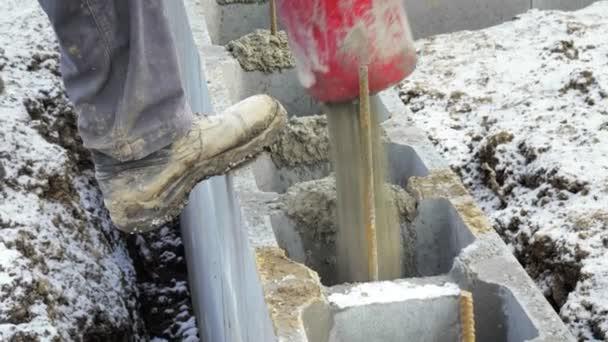 Dělníci pracují na staveniště, zemní práce. Detail čerpadla lití betonu do základů rodinného domu. Čerpadlo na beton, obloha pozadí