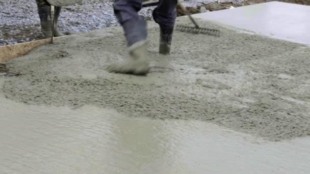 Dělníci pracují na staveništi, pozemní práce. Detail lití čerpadla betonu do základů rodinného domu. Betonové mix čerpadlo pracuje na podkladové desce, obloha v pozadí