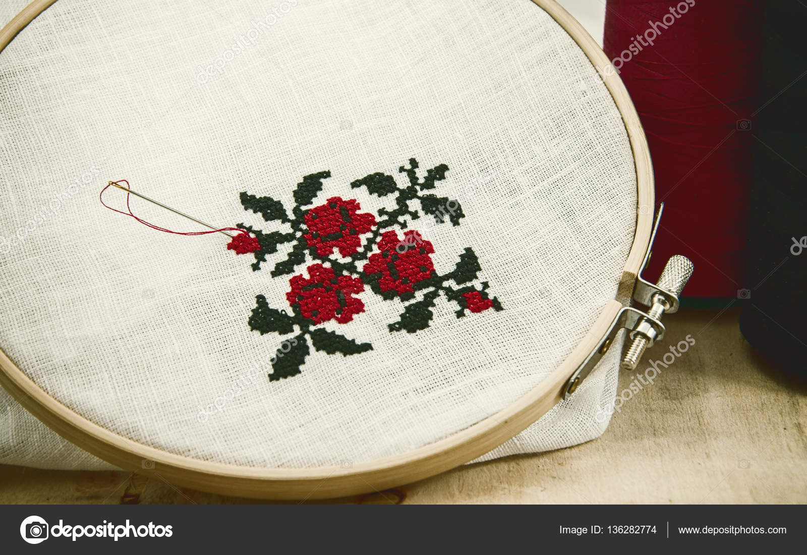 Hand embroidery cross stitch flower ornament on a white fabric ...