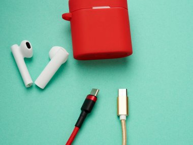 red charging box and sticks headphones on a green background, close up