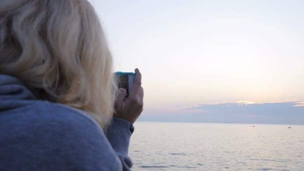 Giovane donna riprese con una telecamera contro il cielo di tramonto Slow Motion