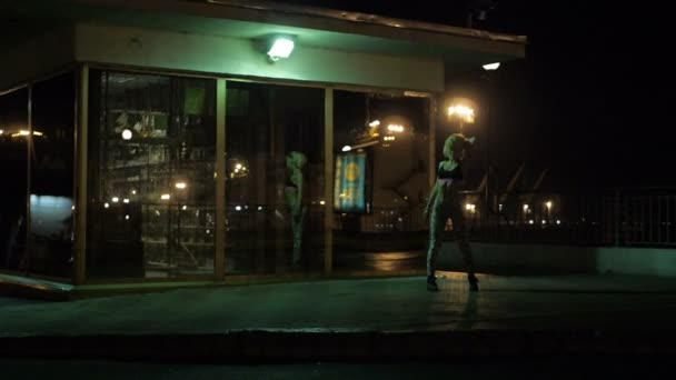 Girls dancing twerk in a public place in a mirror on the night street