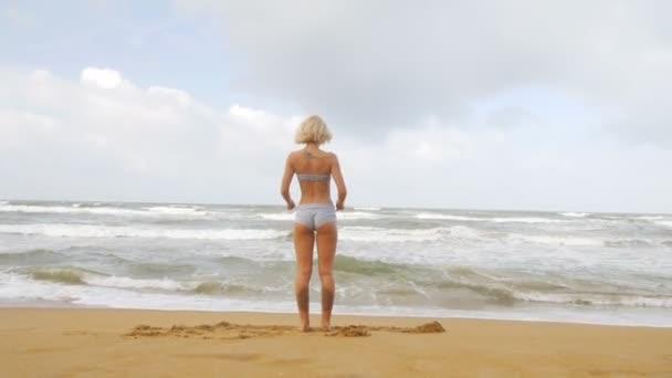 junge Frau mit schlanker Figur dehnt sich auf See