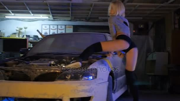 Tanec twerk v garáži nedaleko pneumatiky a auta super sexy provokativní Blondýnka
