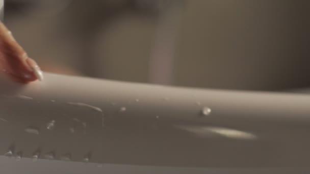 Kapky vody na zápěstí žena s manikúru na pozadí bílé bathtab