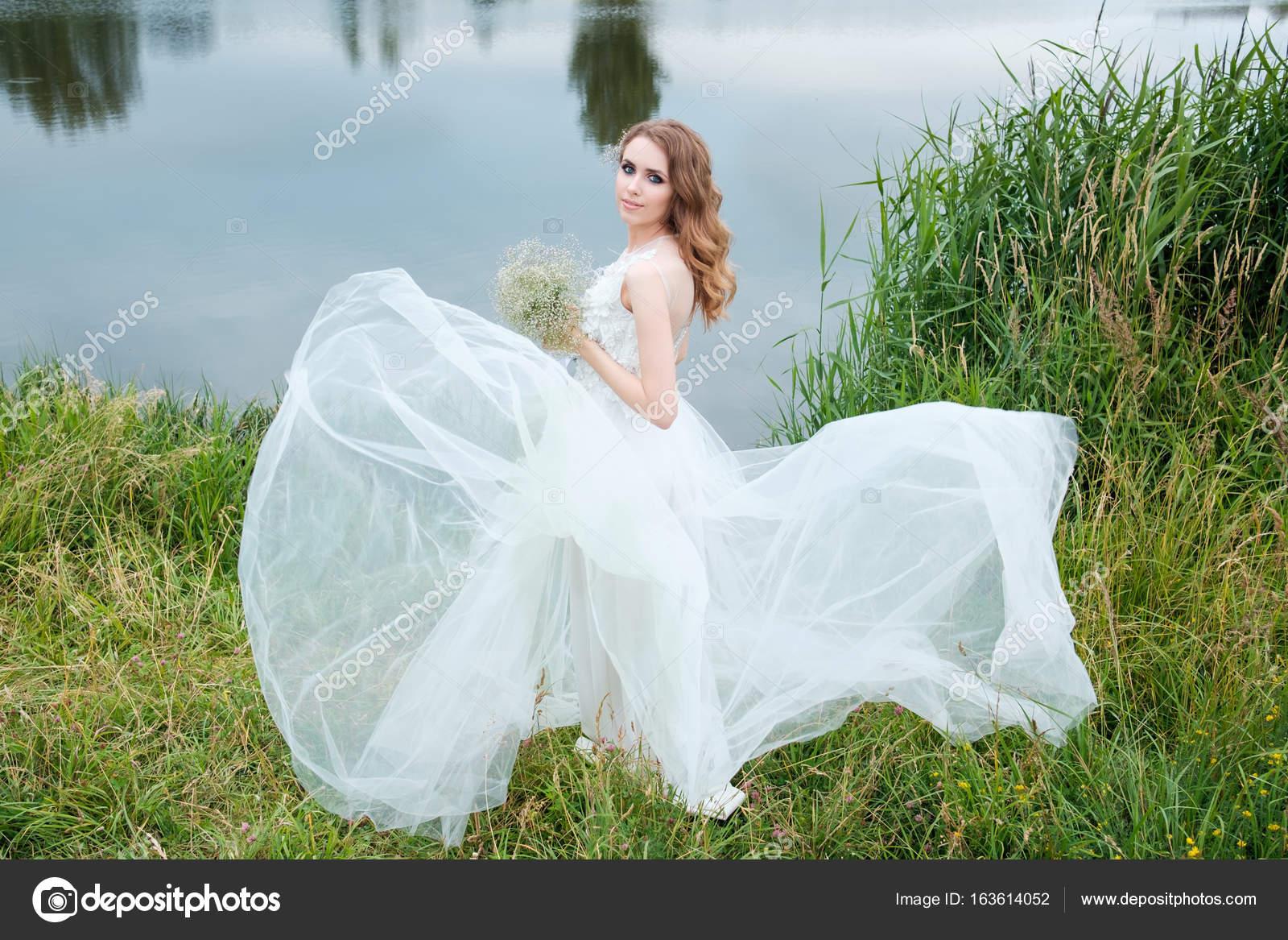 joven mujer bonita (novia) en blanco vestido de novia al aire libre ...