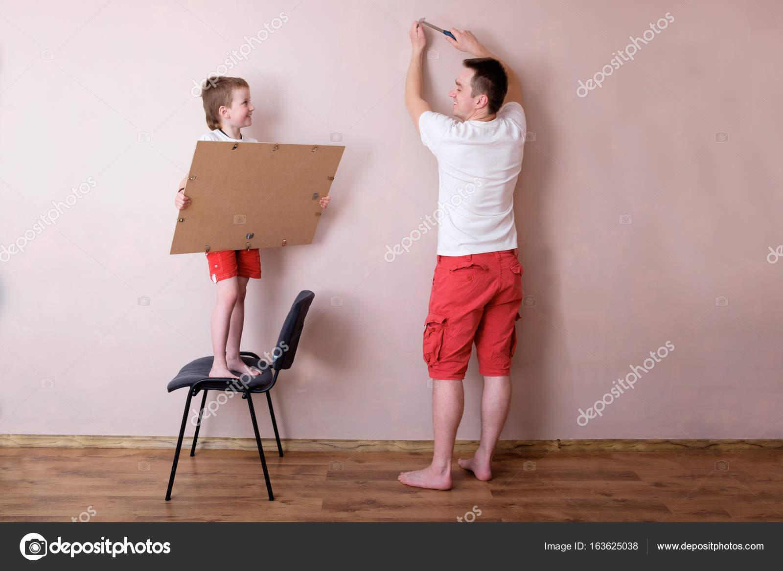 hijo a padre para colgar el cuadro en la pared, el concepto de ...