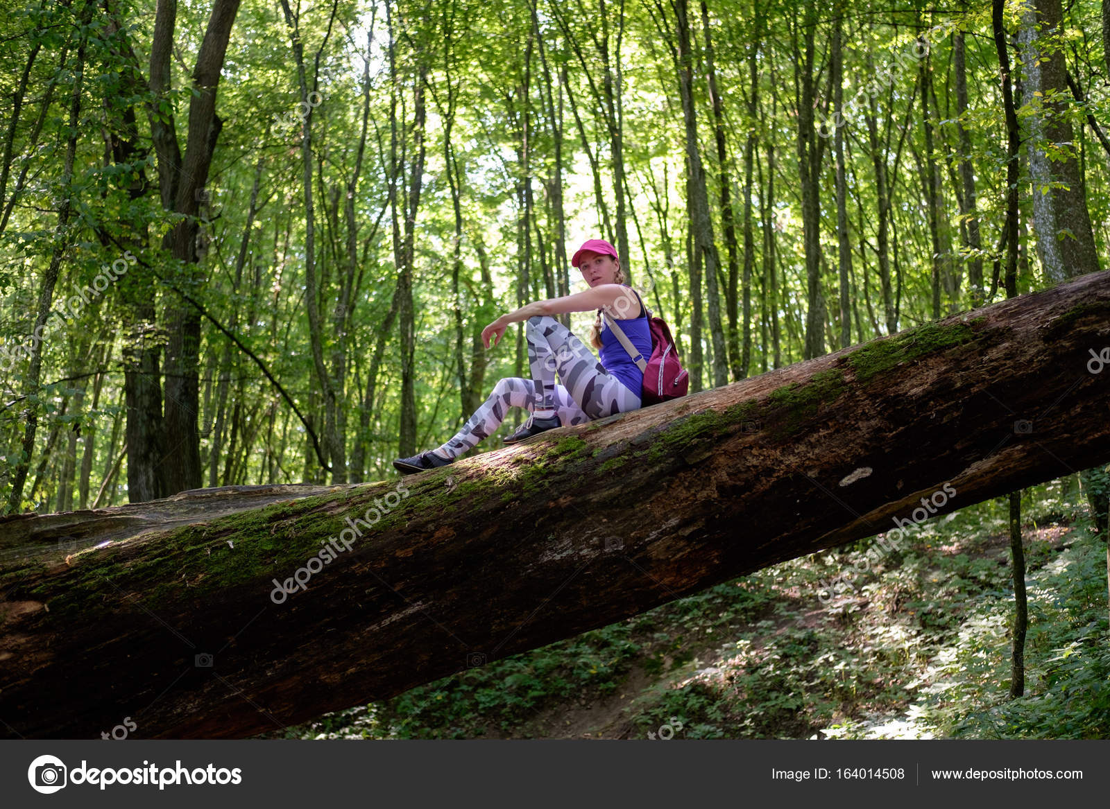Girl hiking in forest, climbing up to the log — Stock Photo