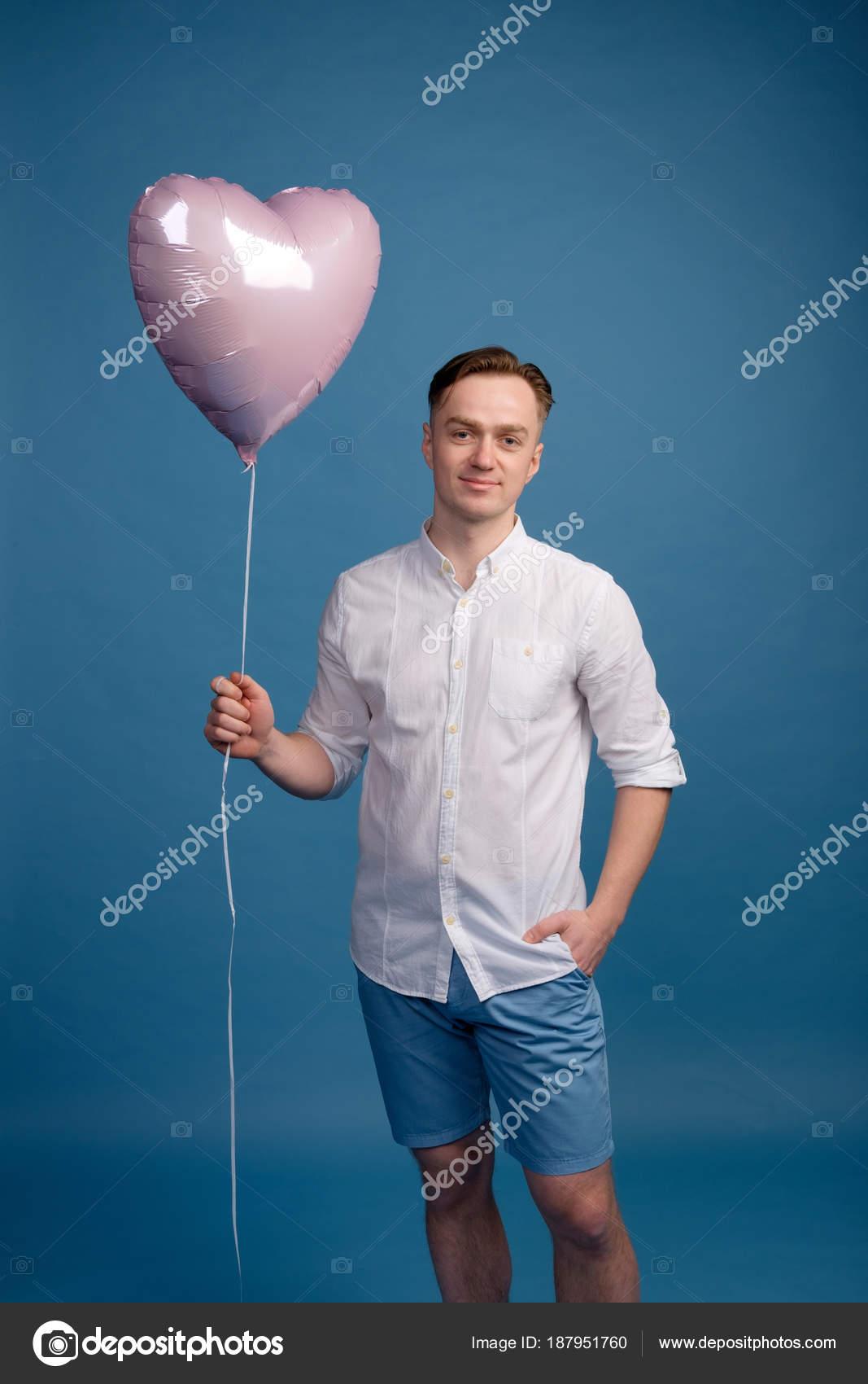 a2e2a0926 Hermoso caucásico hombre en camisa blanca sonriendo y sosteniendo en globo  manera saludos de la forma de corazón de color rosa, azul fondo — Foto de  ...