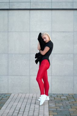 Portrait of young positive sporty girl wearing black sportswear, red leggings and trendy white sneakers. Outdoor shot on grey wall background.