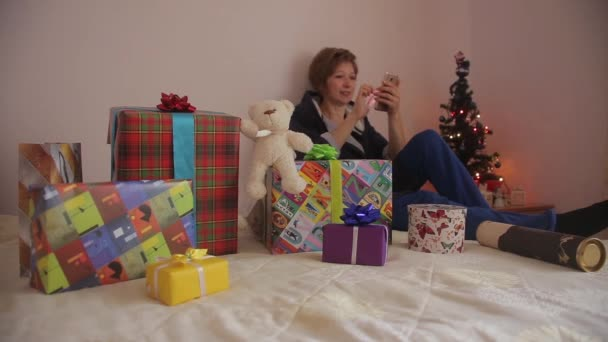 Woman with gifts. Using smartphone to shopping online.