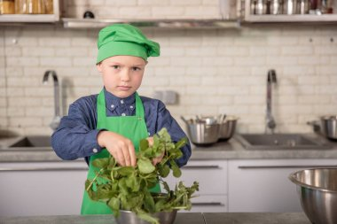 Little boy in a chefs hat and apron at kitchen.