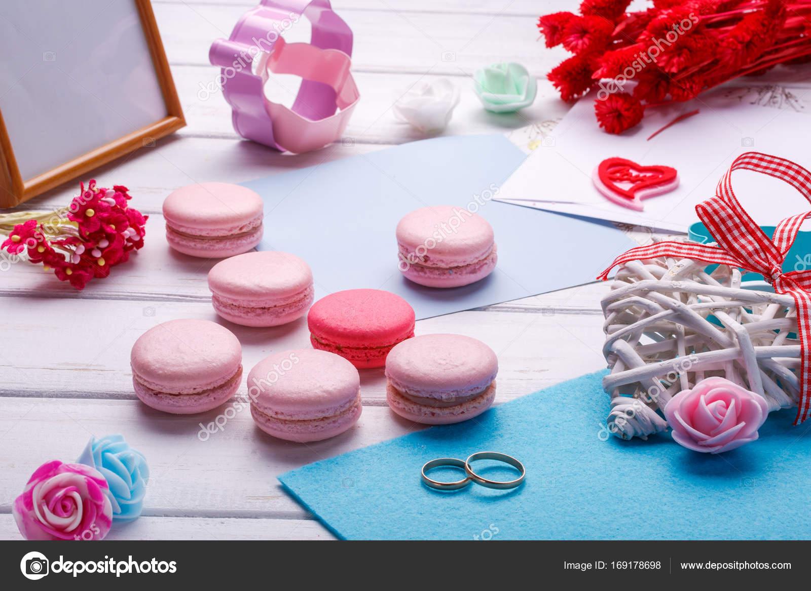 Rosa herzförmige Makronen und Trauringe mit Postkarte, Fotorahmen ...