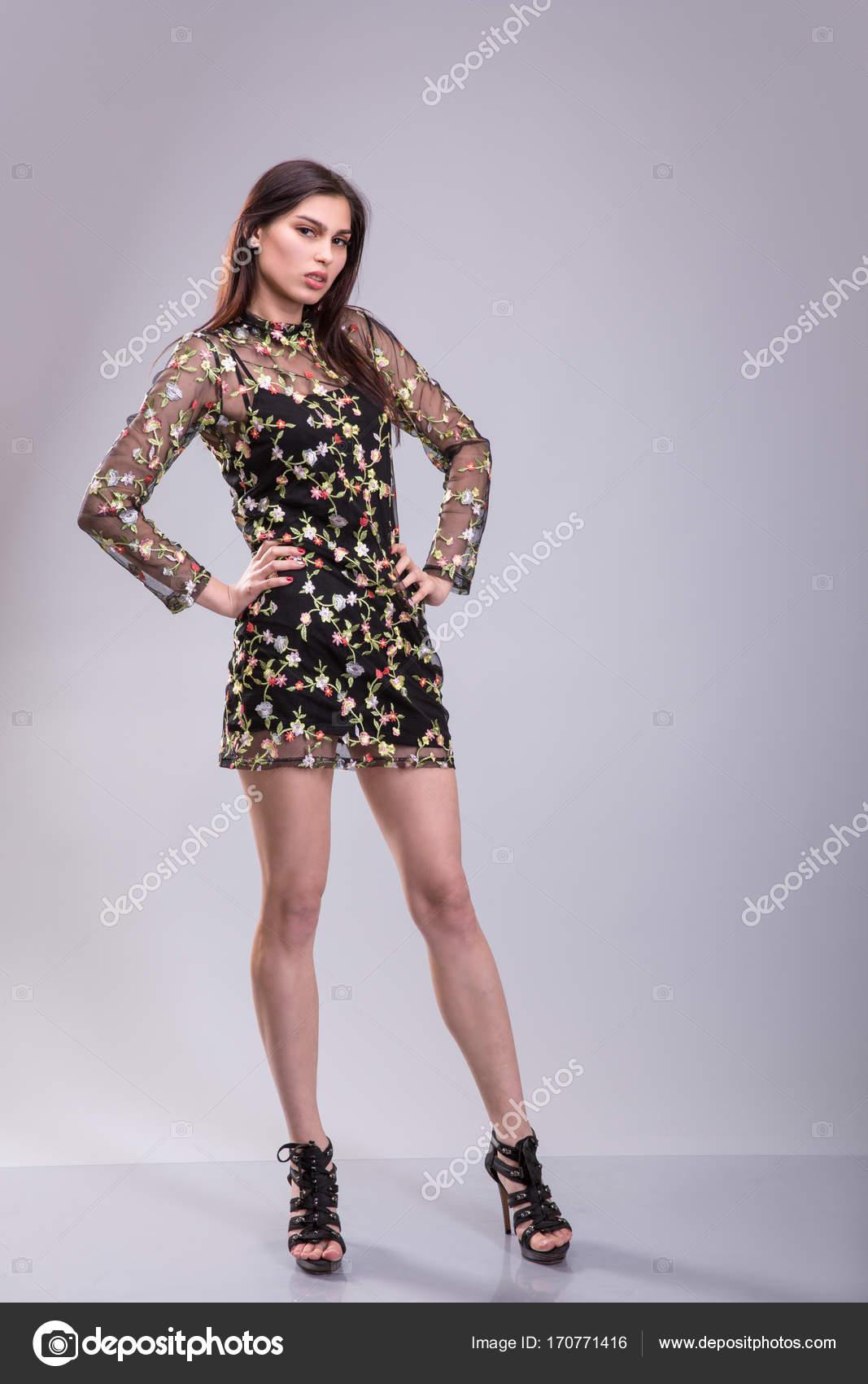Schöne junge Frau trägt ein kleines schwarzes Kleid posiert ...