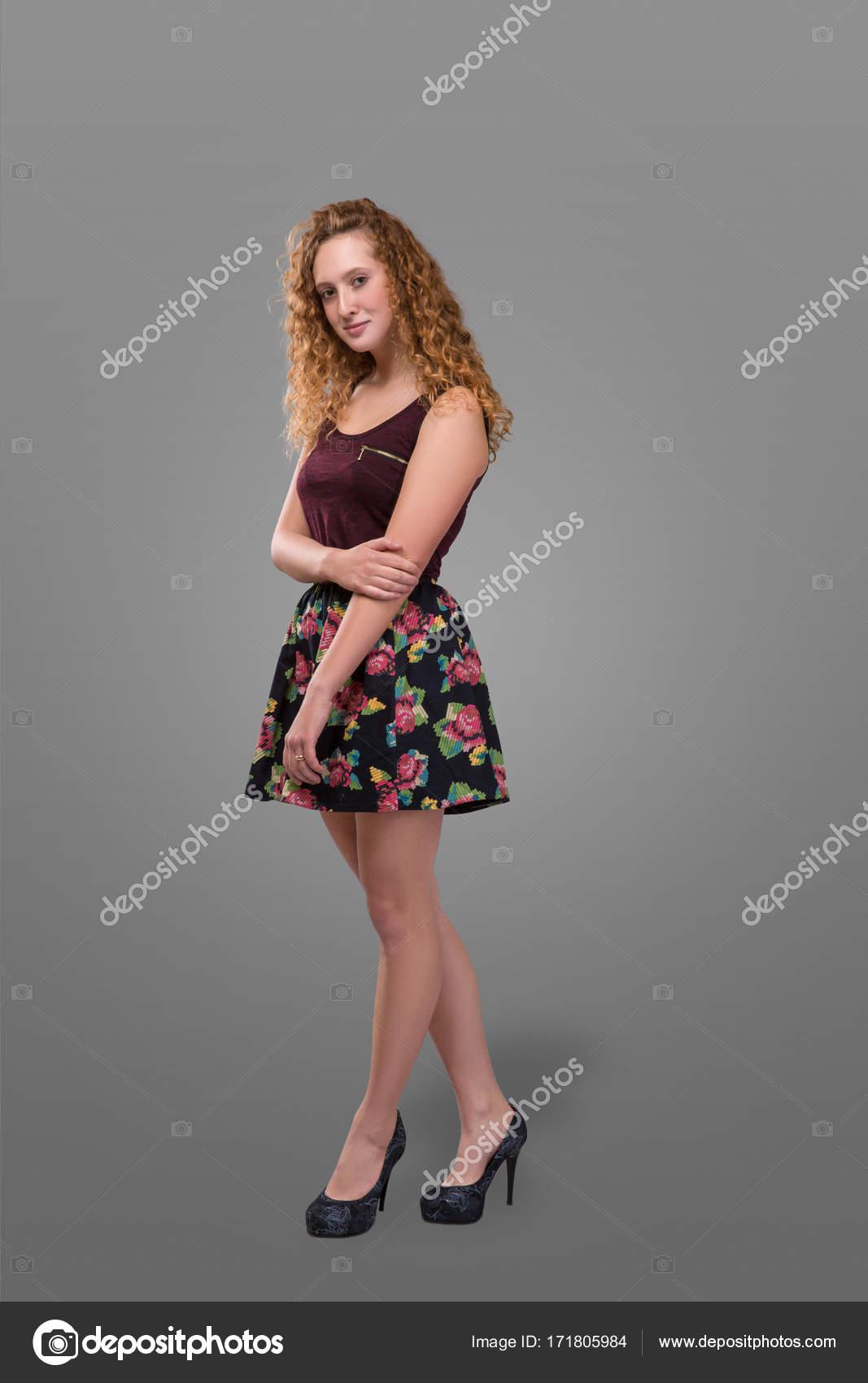 33150ef9bc Bonita talla grande joven pelirroja y pelo rizado niña con falda corta con  estampado floral aislado sobre fondo gris. Además de su tamaño - imágenes   faldas ...