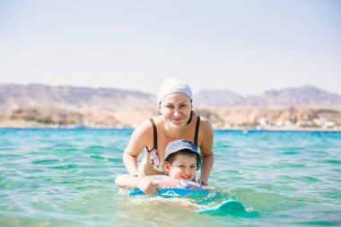 mother and baby swimming with inflatable ring in sea. holiday. vocation