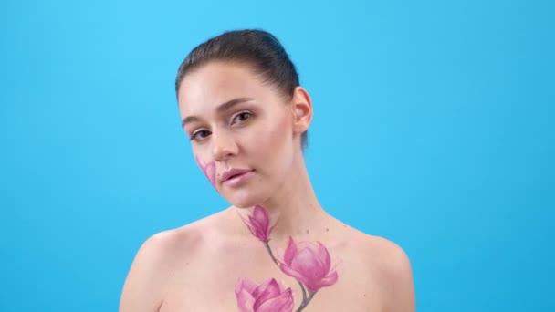 Test Art: nő festett magnólia az arcán és bordák. Virág a testen. Kék háttér