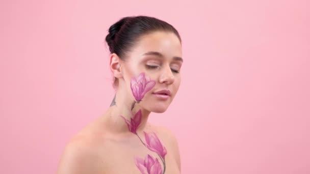 Test Art: nő festett magnólia az arcán és bordák. Virág a testen. Portré rózsaszín háttér