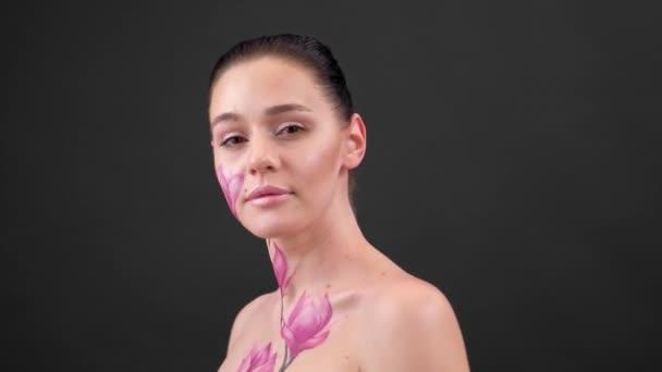 Test Art: nő festett magnólia az arcán és bordák. Virág a testen. Portré fekete háttér