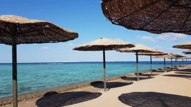 Beach with deck sunshades, umbrellas. Beach, sea, sand, wave. Seascape ocean and beautiful beach paradise, blue sky, clouds. Video Travel concept