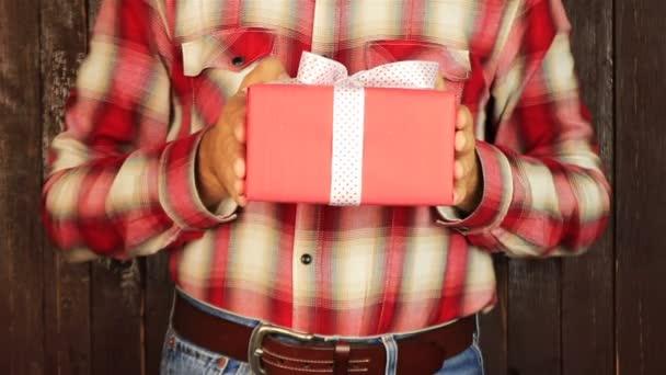 Mladý muž dává dar na dřevěné pozadí. Červená dárková krabička s bílou mašlí otevření. Blahopřát šťastný nový rok, Veselé Vánoce, Šťastný Valentýna, dárky dárky