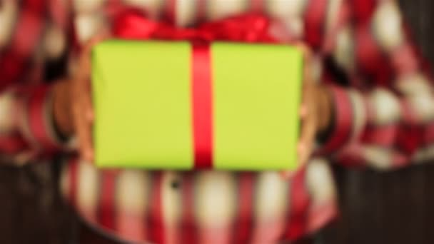 Young man gives a gift on wooden background. Green gift box with red ribbon opening. Congratulate Happy New Year, Merry Christmas, Happy Valentines Day, presents gifts