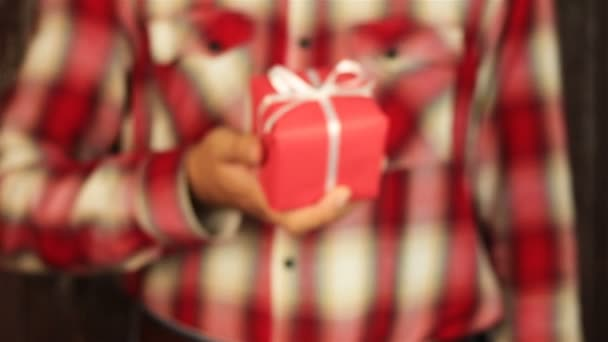 Young man gives a gift on wooden background. Red gift box with white ribbon opening. Congratulate Happy New Year, Merry Christmas, Happy Valentines Day, presents gifts