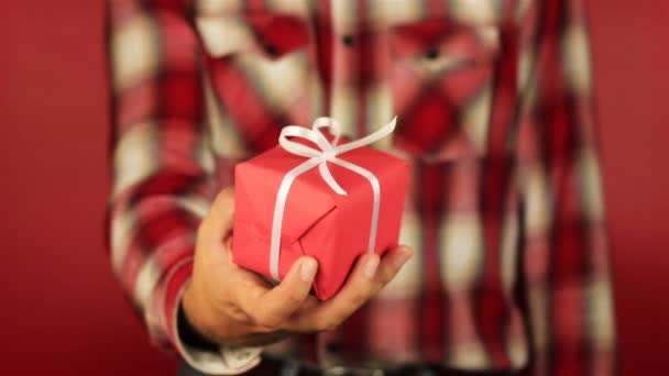 Young man gives a gift on red background. Red gift box with white ribbon opening. Congratulate Happy New Year, Merry Christmas, Happy Valentines Day, presents gifts
