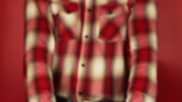 junger Mann schenkt auf rotem Hintergrund. roter Geschenkkarton mit Öffnung des weißen Bandes. Glückwunsch zum neuen Jahr, frohe Weihnachten, frohe Valentinstage, Geschenke