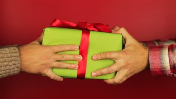 Young man gives a gift on red background. Green gift box with red ribbon opening. Congratulate Happy New Year, Merry Christmas, Happy Valentines Day, presents gifts