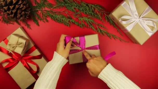 Pohled shora ruce balicí vánoční dárky na červeném pozadí shora. Dárkové balené do balicího papíru a svázané fialovou stuhou