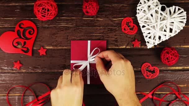 Junger Mann faltet den Umschlag für Valentinstagsgeschenk von oben auf einem Holztisch auf