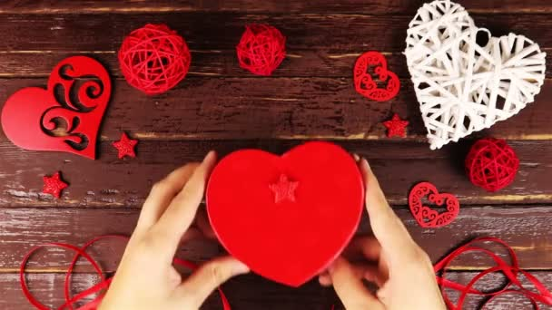 Top view hands puts a box of heart shaped to Valentines Day at wooden desk from above