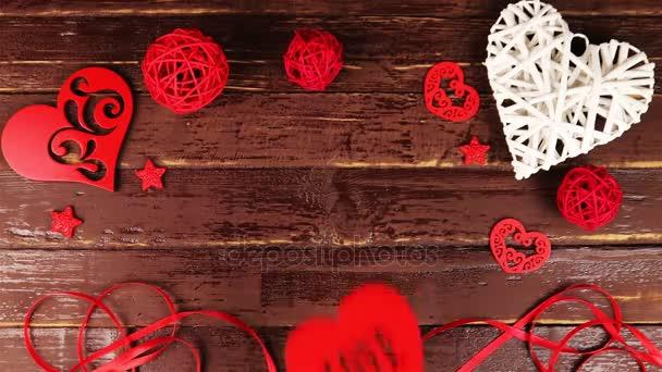 Pohled shora ruce dá srdce z kartonu s nápisem love Valentines den na dřevěný stůl z výšky