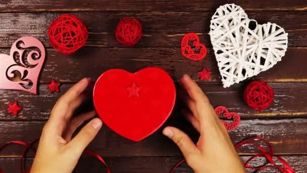 Felülnézet fiatalember megnyílik a doboz az alakja a szív és a belsejében a szív készült karton a szót szerelem Valentin nap ajándék, egy fából készült asztal